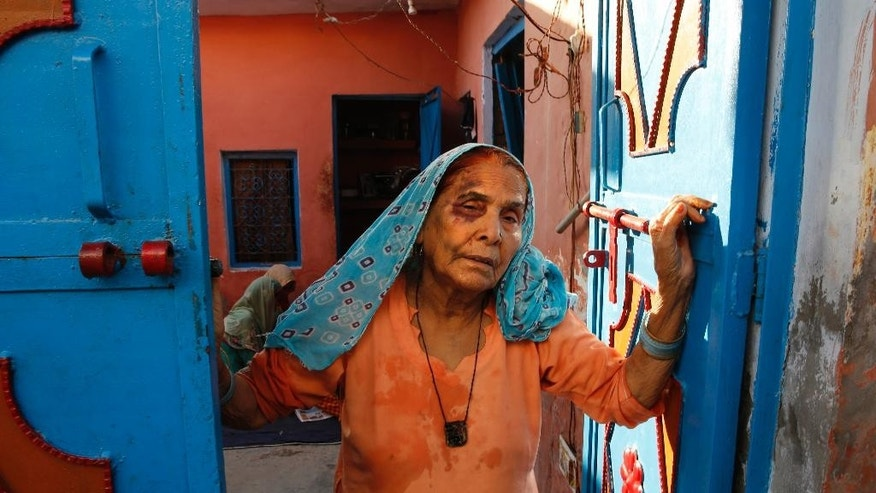 FILE- In this Sept. 30, 2015 file photo, a bruised Asgari Begum, mother of 52-year-old Muslim farmer Mohammad Akhlaq,killed over rumors he slaughtered a cow stands by the entrance of her home in Bisara, a village about 45 kilometers (25 miles) southeast of the Indian capital of New Delhi . Government investigators have found the fatal mob attack of a Muslim man over rumors he slaughtered a cow was premeditated, and not a spontaneous act stemming from heightened emotion and religious devotion as many Hindu nationalist politicians have claimed. (AP Photo/Manish Swarup)