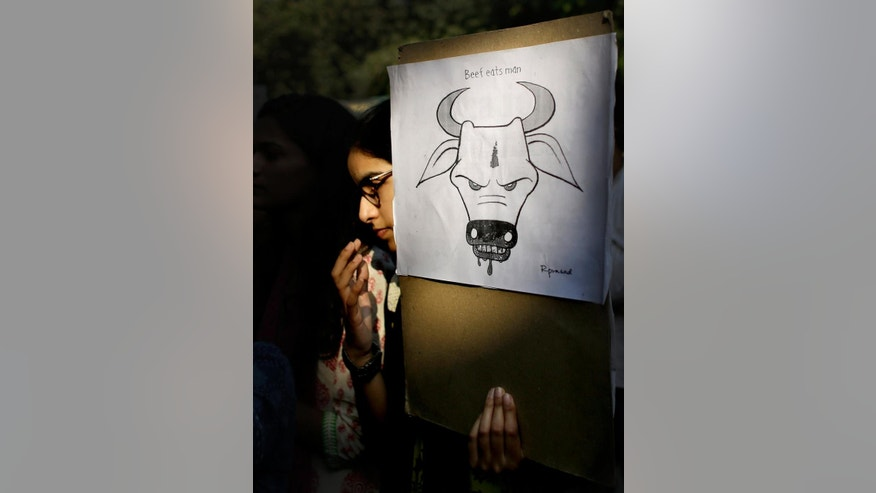 FILE- In this Oct. 2, 2015 file photo, student activists holds a placard during a protest denouncing the killing of a 52-year-old Muslim farmer Mohammad Akhlaq, in New Delhi, India. Government investigators have found the fatal mob attack of a Muslim man over rumors he slaughtered a cow was premeditated, and not a spontaneous act stemming from heightened emotion and religious devotion as many Hindu nationalist politicians have claimed. (AP Photo/Altaf Qadri, file)