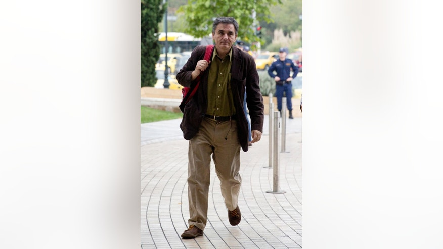 Greece's finance minister Euclid Tsakalotos arrives for a meeting with representatives of the European Central Bank, International Monetary Fund, European Commission and European Stability Mechanism in Athens, Wednesday, Oct. 21, 2015. Greece's international debt inspectors are reviewing the country's progress on reforms it must make to receive more funds from its third bailout. (AP Photo/Petros Giannakouris)