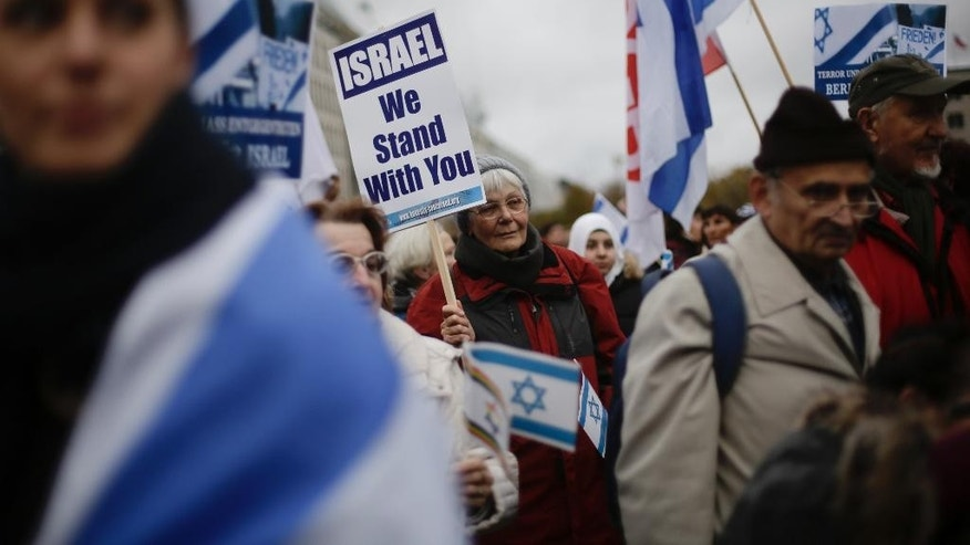 People attend a demonstration demanding solidarity with Israel at the Brandenburg Gate in Berlin, Germany, Tuesday, Oct. 20, 2015. U.N. Secretary-General Ban Ki-moon called for calm during a visit to Jerusalem on Tuesday ahead of meetings with Israeli and Palestinian leaders, in a high-profile gambit to bring an end to a monthlong wave of violence.  (AP Photo/Markus Schreiber)