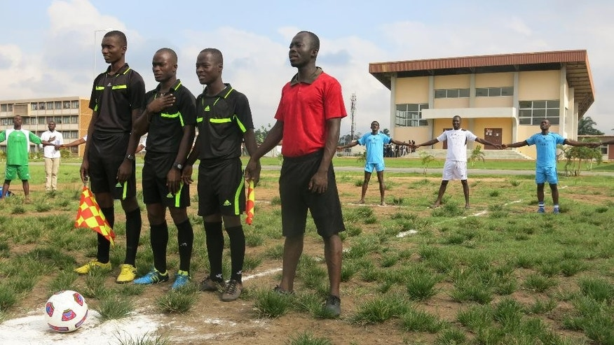 In this photo taken Friday Oct. 16, 2015, match officials wait before an exhibition match between soccer team members of  FESCI in white and rival unions team at the  university in Abidjan, Ivory Coast. Ten years ago, the student union at Ivory Coast's largest university began resembling a brutal pro-government militia, bringing it full circle from the days when its leaders were arrested by officials from a previous government who were seeking to clamp down on protests. Now, FESCI _ as the union is known by its initials in French _ is on a charm offensive intended to show that it has abandoned its violent ways.  (AP Photo/Robbie Corey-Boulet)