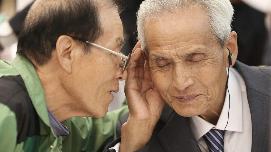 South Korean Song Byong-chan, 76, left, whispers to his North Korean brother Song Byong Sang, 82, during the Separated Family Reunion Meeting at the Diamond Mountain resort in North Korea, Wednesday, Oct. 21, 2015. Hundreds of elderly Koreans from divided North and South began three days of reunions Tuesday with loved ones many have had no contact with since the war between the countries more than 60 years ago. (Kim Do-hoon/Yonhap via AP) KOREA OUT