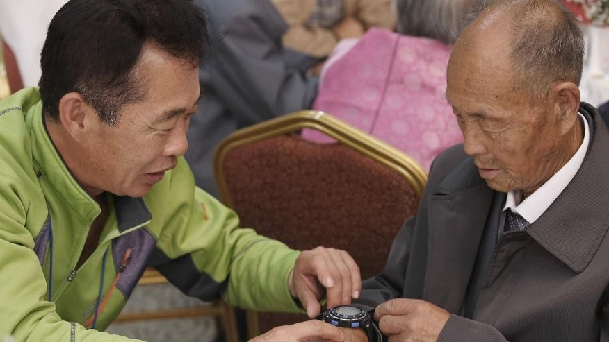South Korean Kim Chun-yeol, 54, left, presents a watch to his North Korean uncle Kim Yun Ju,85, during the Separated Family Reunion Meeting at the Diamond Mountain resort in North Korea, Wednesday, Oct. 21, 2015. Hundreds of elderly Koreans from the divided North and South began three days of reunions Tuesday with loved ones, many have had no contact with since the war between the the countries more than 60 years ago. (Kim Do-hoon/Yonhap via AP) KOREA OUT
