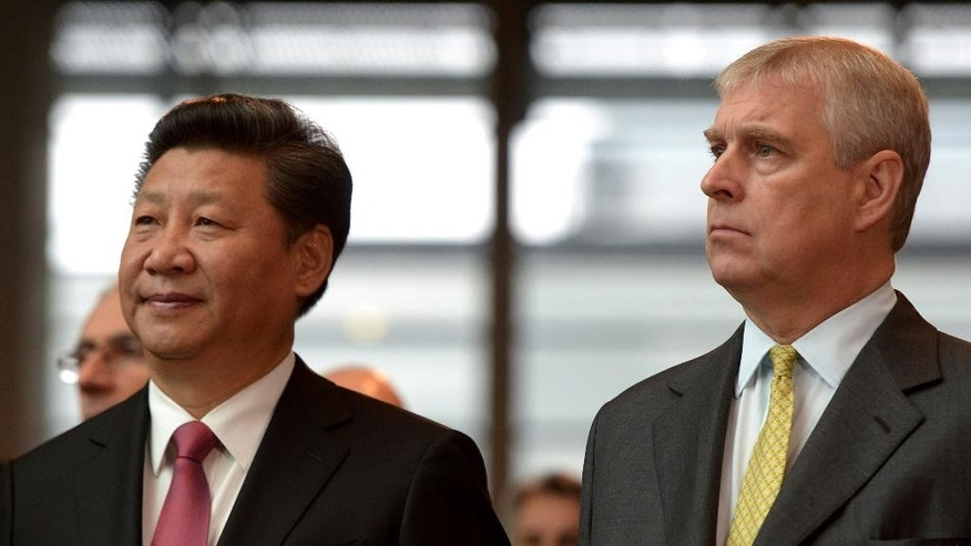 China's President Xi Jinping, left, stands with Britain's Prince Andrew, Duke of York, as they listen to speeches during a visit to Imperial College London, in London, Wednesday, Oct. 21, 2015, on day two of the state visit by the Chinese President. China's state visit to Britain moves from warm toasts and ceremony to cold, hard cash Wednesday, with business deals including a major Chinese investment in the U.K.'s first nuclear power station since the 1980s. (Anthony Devlin/Pool Photo via AP)