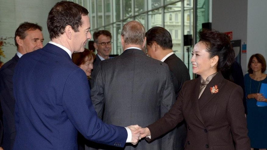 Britain's Chancellor of the Exchequer George Osborne, left,  shakes hands with China's first lady Peng Liyuan, with Prince Andrew, Duke of York at background centre and China's President Xi Jiping background right, during a visit to Imperial College London, in London, Wednesday, Oct. 21, 2015, on day two of the state visit by the Chinese President. China's state visit to Britain moves from warm toasts and ceremony to cold, hard cash Wednesday, with business deals including a major Chinese investment in the U.K.'s first nuclear power station since the 1980s. (Anthony Devlin/Pool Photo via AP)