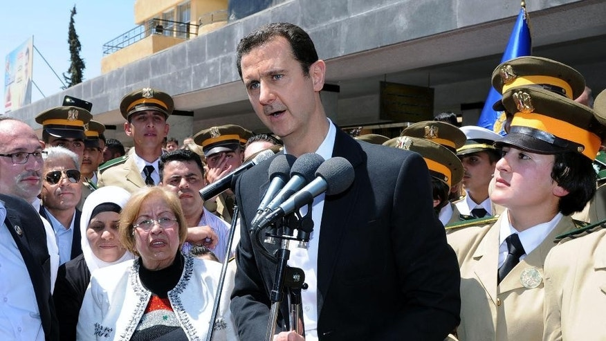 FILE - In this Wednesday, May 6, 2015, file photo released by the Syrian official news agency SANA, Syrian President Bashar Assad speaks during a public appearance at a school in Damascus, Syria. Russia's military intervention in Syria has increasingly bolstered the sense that Bashar Assad may survive the war, and his surprise visit to Moscow, the first time he's left the war-torn country in nearly five years, underscores how emboldened the leader has become. The visit is a brazen show of force by the two allies and a slap in the face of a fumbling U.S. administration whose response on Syria over the past years has been inconsistent and chaotic. (SANA via AP, File)