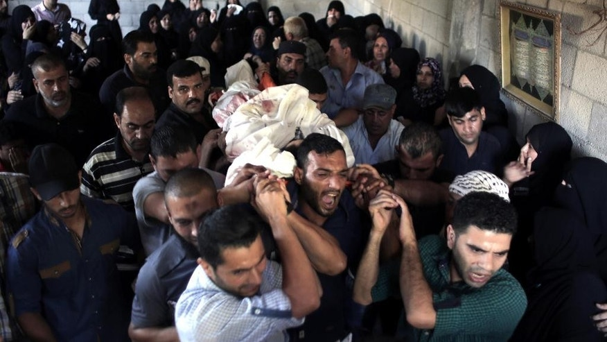 Palestinian mourners chant angry slogans as they carry the body of Ahmed Al-Serhi, 27, who was killed during clashes with Israeli troops near the Israeli border with Gaza, during his funeral outside the family house in Deir el-Balah, in the central Gaza Strip, Wednesday, Oct. 21, 2015. (AP Photo/ Khalil Hamra)