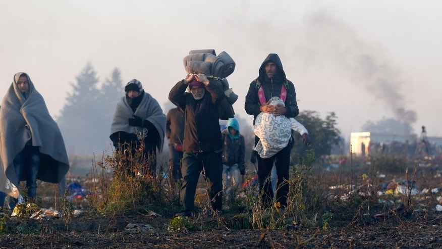 Migrants walk in the field near a border line between Serbia and Croatia, near the village of Berkasovo, Serbia, Wednesday, Oct. 21, 2015. Croatia, which has erected relatively few shelters along its borders with Serbia and Slovenia, directed thousands into special trains and bus convoys Tuesday to Slovenia in an apparently concerted effort to clear a backlog built up since Saturday, when Hungary closed its borders with Croatia. (AP Photo/Darko Vojinovic)