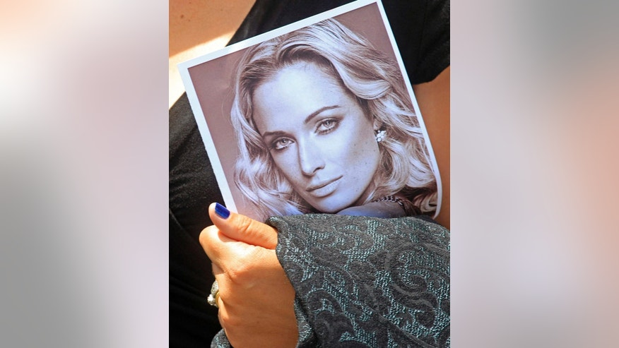 FILE - In this Tuesday, Feb. 19, 2013 file photo a mourner holds a funeral program with a portrait of Reeva Steenkamp, the late girlfriend of Oscar Pistorius, in Port Elizabeth, South Africa. (AP Photo/Schalk van Zuydam-file)