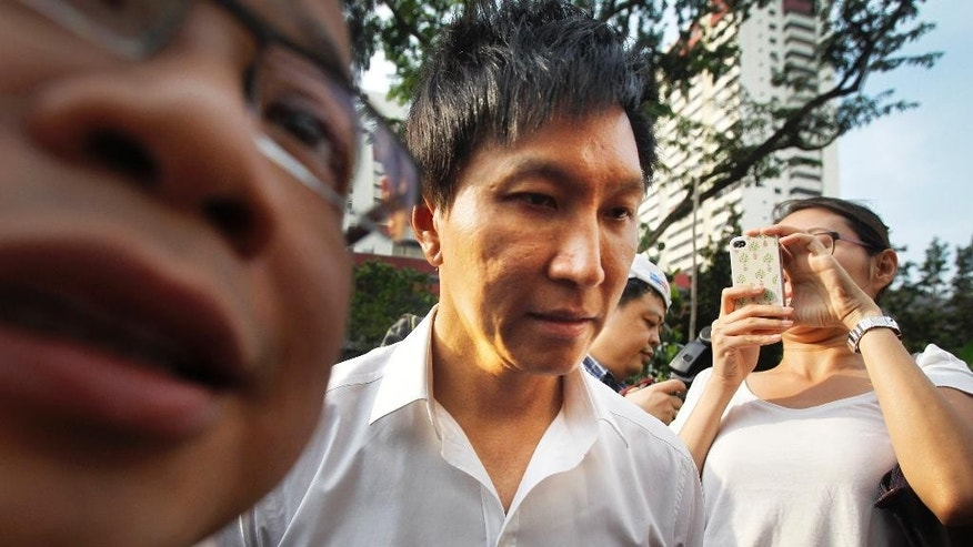 In this July 12, 2012, file photo, City Harvest Church founder Kong Hee, center, is surrounded by the media as he arrives at the Subordinate Courts in Singapore. The founder of the popular Singapore church has been found guilty Wednesday, Oct. 21, 2015, of misappropriating about $35 million in donations to support his wife's singing career in Asia before helping her break into the U.S. market for evangelization purposes. (AP Photo/Wong Maye-E, File)