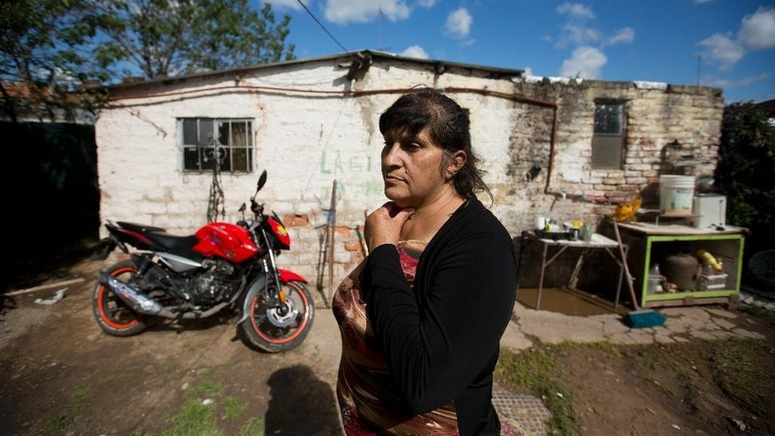 "Nora Beatriz Diaz stands outside her home in Hurlingham in the province of Buenos Aires, Argentina, Tuesday, Oct. 20, 2015. Diaz says her choice for president in Sunday's election was essentially decided six years ago, when she was hired by the government jobs program. Now 55, the mother of two struggled for years to make ends meet. But through the ""Argentina Works"" program created by President Cristina Fernandez's government, Diaz got a job cleaning and doing light construction. ""If I lose this job, I'll go back to zero,"" Diaz said of her $275-a-month salary. ""This government has to stay in power."" (AP Photo/Victor R. Caivano)"