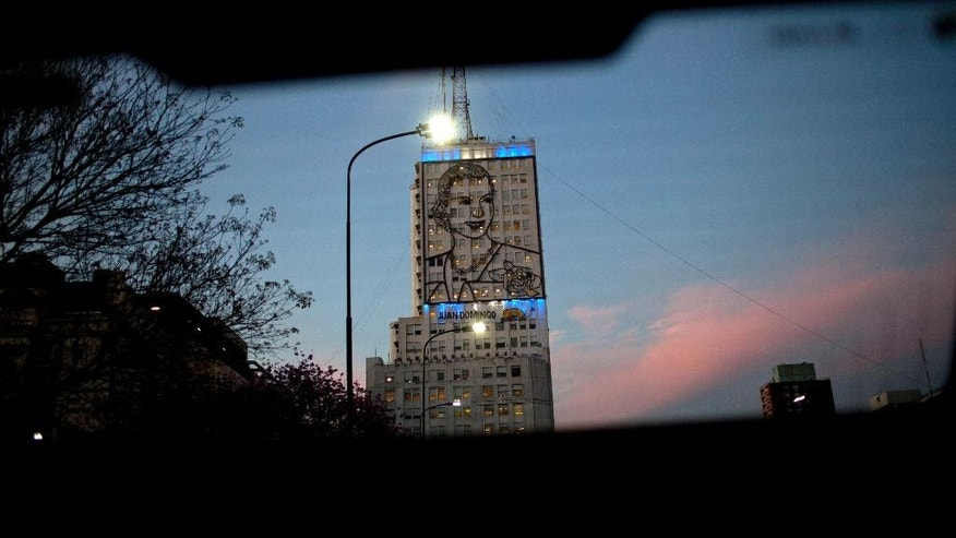 Argentina's social development ministry building is covered by an iron portrait of the late first lady Eva Peron, wife of former President Juan Domingo Peron, seen through a car's rear window in Buenos Aires, Argentina, Tuesday, Oct. 20, 2015. Today, an estimated 15 million Argentines, or about 35 percent of the population, receive some kind of direct financial assistance from the government, according to researchers at the Catholic University of Argentina. Argentina will hold its first round presidential elections on Oct. 25. (AP Photo/Natacha Pisarenko)