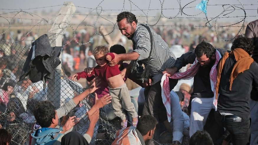 FILE - In this Sunday, June 14, 2015 file photo, a Syrian refugee carries a baby over the broken border fence into Turkey after breaking the border fence and crossing from Syria in Akcakale, Sanliurfa province, southeastern Turkey. A Kurdish official says a new administration has been formed for a majority Sunni-Arab town controlled by Syrian Kurds, expanding the ethnic group's semi-autonomous administration in northern Syria. (AP Photo/Lefteris Pitarakis, File)