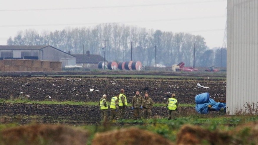Defence personnel stand in a field, at the scene of a jet crash, in Redmere, Cambridgeshire, England, Wednesday Oct.  21, 2015. The pilot of a U.S. Marine Corps F-18 was killed Wednesday when the plane crashed near a British air base in eastern England, U.S. and British officials said. (Chris Radburn/PA via AP) UNITED KINGDOM OUT