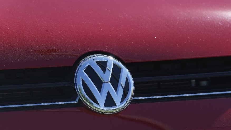 FILE - In this Sept. 24, 2015 file photo, the grille of a Volkswagen is decorated with the iconic company logo at on the lot of a VW dealership in Boulder, Colo. An expanding investigation into Volkswagen's emissions-cheating scandal launched by state attorneys general could last years and will likely end in a negotiated settlement.  (AP Photo/Brennan Linsley, File)