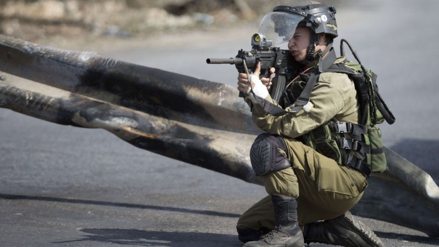 Oct. 20, 2015: An Israeli solder takes aim, during clashes with Palestinians near Ramallah, West Bank.
