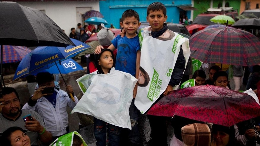 In this Oct. 18, 2015 photo, kids waits in the rain for a campaign rally to start for presidential candidate Sandra Torres, a former first lady from the National Unity of Hope party, in Mixco, Guatemala. Whoever wins the Oct. 25 presidential runoff will have to respond quickly to widespread demands for deep institutional reform in a country fed up with corrupt politics as usual. (AP Photo/Moises Castillo)