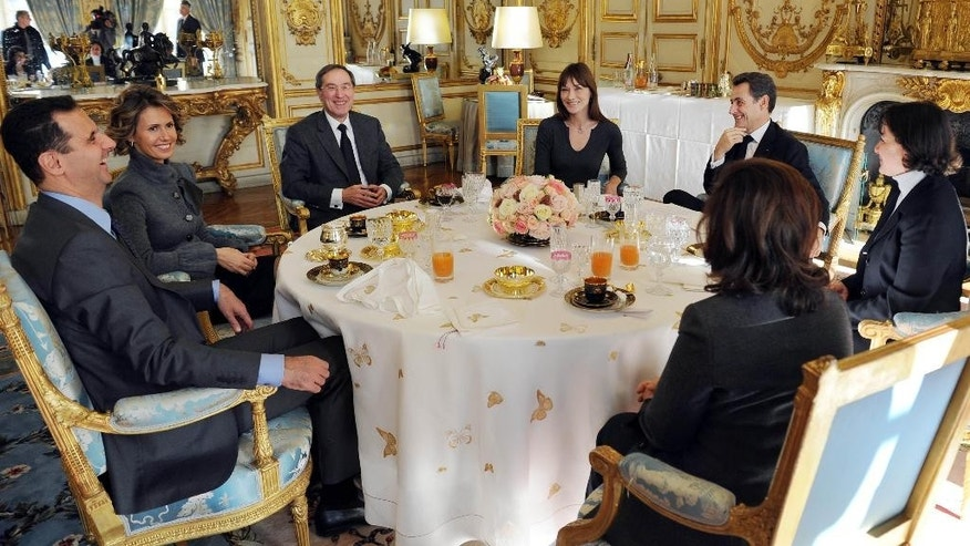 FILE - In this Thursday Dec. 9, 2010 file photo, French president Nicolas Sarkozy, second right, his wife Carla Bruni-Sarkozy, center, and his advisor Claude Gueant, third left, share a working lunch with Syrian President Bashar al-Assad, left, and his wife Asma, second left, at the Elysee Palace in Paris. Russia's military intervention in Syria has increasingly bolstered the sense that Bashar Assad may survive the war, and his surprise visit to Moscow, the first time he's left the war-torn country in nearly five years, underscores how emboldened the leader has become. The visit is a brazen show of force by the two allies and a slap in the face of a fumbling U.S. administration whose response on Syria over the past years has been inconsistent and chaotic. (AP Photo/Franck Fife, Pool, File)