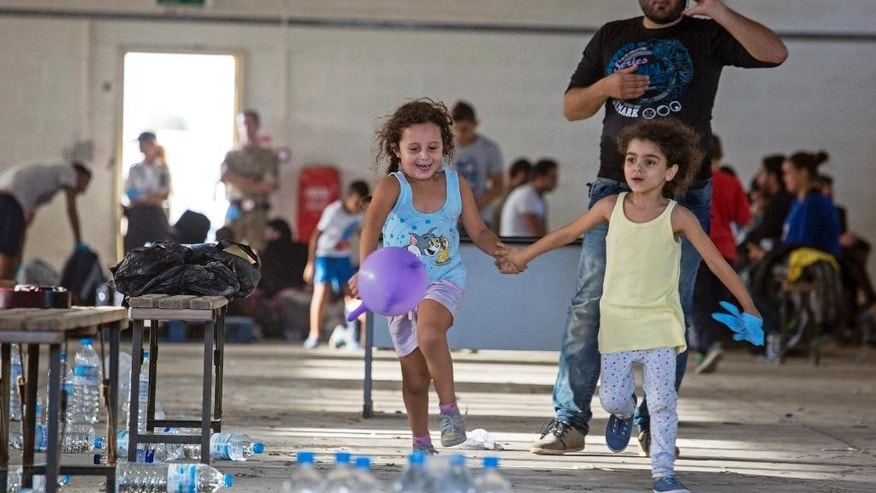 "Syrian migrants are temporarily housed at a warehouse after coming ashore at RAF base Akrotiri, Cyprus, Wednesday, Oct. 21, 2015. Cyprus' interior ministry says a total of 114 people, including 28 children and 19 women, were aboard two fishing boats that landed at a British air base on the island's southern coast on Wednesday morning, all of whom are now at RAF Akrotiri. British Bases authorities said Wednesday that a 2003 agreement holds the Cyprus government responsible for such arrivals on two military bases the island hosts. It also said this incident underlines the need for a comprehensive approach to Europe's migration crisis that would provide humanitarian assistance to Syria and neighboring countries, disrupt trafficking gangs and ""address the root causes of instability."" (Jack Hill/Pool Photo via AP)"