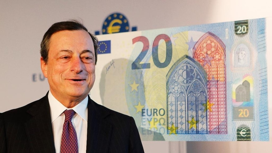 File - In this Tuesday, Feb. 24, 2015 file photo, Mario Draghi, the president of the European Central Bank, stands next to a copy of a 20 euro banknote in Frankfurt, Germany. On Thursday, Oct. 22, 2015, Draghi hinted that the bank may expand its monetary stimulus at its December meeting in order to shore up the ailing recovery in the 19-country eurozone. (AP Photo/Michael Probst, File)