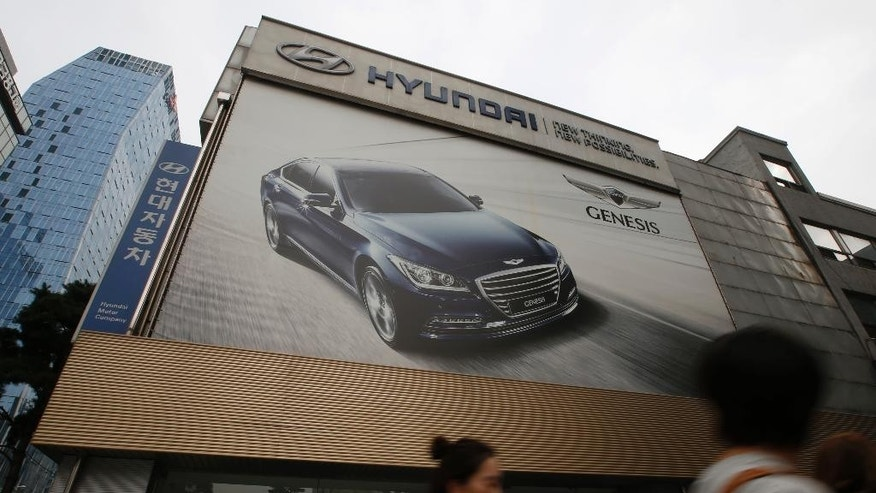 People walk by Hyundai Motor's showroom in Seoul, South Korea, Thursday, Oct. 22, 2015. Hyundai Motor Co. reported Thursday its lowest quarterly earnings in more than five years after losing ground to local brands in China and underestimating strong demand for SUVs. (AP Photo/Lee Jin-man)
