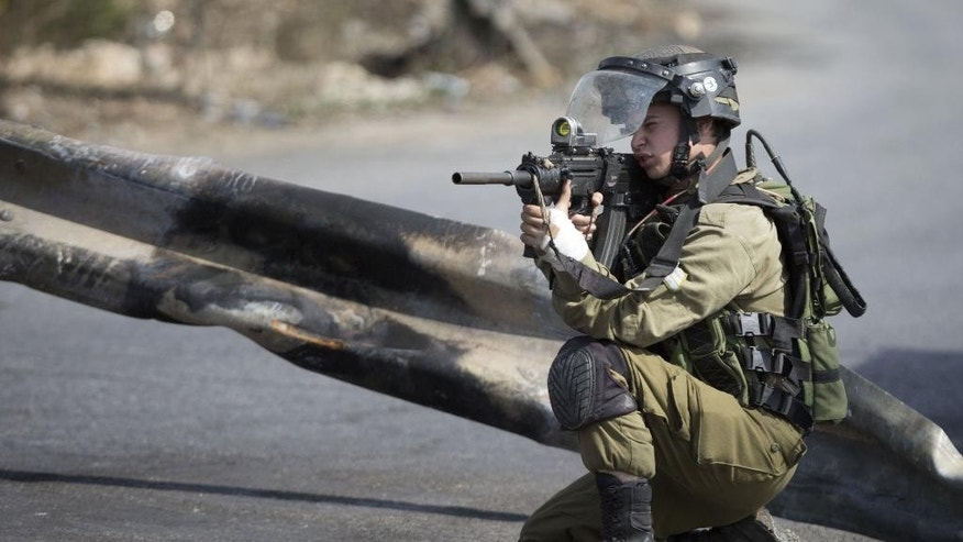 An Israeli solder takes aim, during clashes with Palestinians near Ramallah, West Bank,  Tuesday, Oct. 20, 2015. U.N. Secretary-General Ban Ki-moon called for calm during a surprise visit to Jerusalem on Tuesday ahead of meetings with Israeli and Palestinian leaders, in a high-profile gambit to bring an end to a monthlong wave of violence. (AP Photo/Majdi Mohammed)