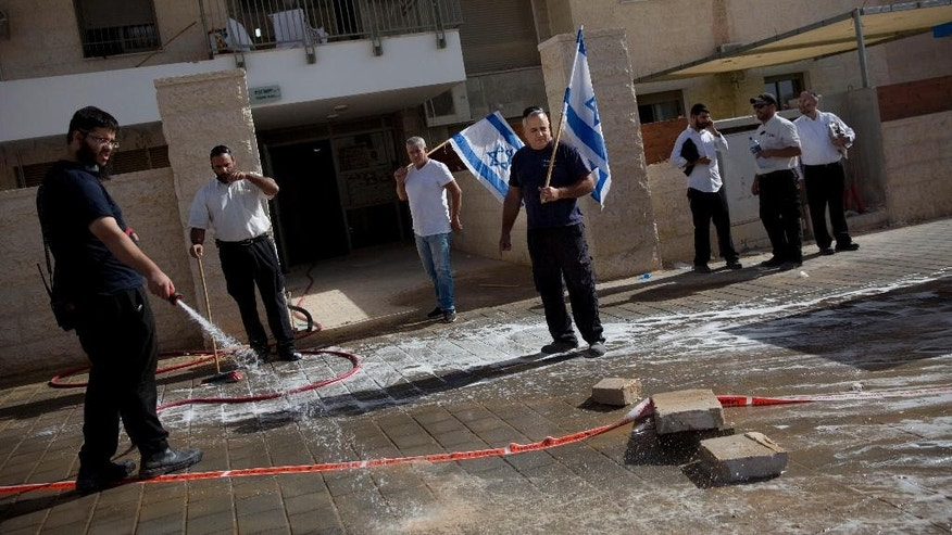 An Israeli man cleans blood stains at the scene of a stabbing attack in Beit Shemesh, central Israel, Thursday, Oct. 22, 2015. Police say two Palestinians stabbed an Israeli man in the city of Beit Shemesh after attempting to board a bus ferrying children to school. Police then shot the attackers. (AP Photo/Oded Balilty)
