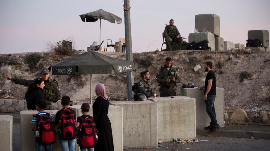 Israeli border police check Palestinian's identification cards at a checkpoint as they exit the Arab neighborhood of Issawiyeh in Jerusalem, Thursday, Oct. 22, 2015. Israel has beefed up security across the country, sending hundreds of soldiers to back up thousands of police officers. Police have erected concrete barriers and checkpoints at the entrance to Arab areas of east Jerusalem, where many of the attackers are from. (AP Photo/Oded Balilty)
