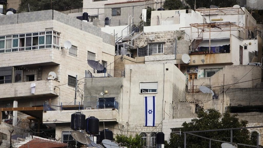 In this Monday, Oct. 19, 2015, photo, an Israeli flag hangs on the wall of a building that was taken over by Israeli settlers after Palestinian families were evicted in the Silwan neighborhood of east Jerusalem. The eviction is part of a house-by-house battle by Jewish settlement organizations, according to some with government backing, to prevent Arab areas in Jerusalem's ancient heart from ever becoming part of a Palestinian state. (AP Photo/Mahmoud Illean)