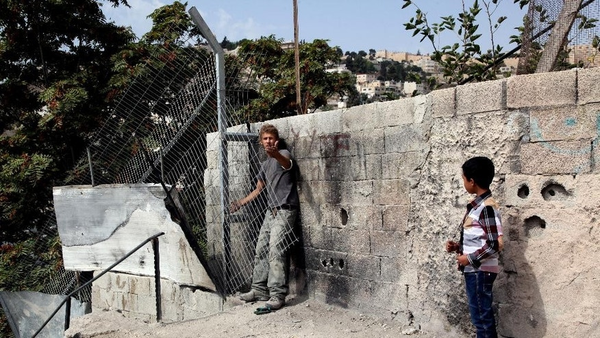 In this Tuesday, Oct. 20, 2015, photo Mohammed Abu Nab, 9, watches as an Israeli settler installs a fence around the house Abu Nab's family was evicted from in the Silwan neighborhood of east Jerusalem. The eviction is part of a house-by-house battle by Jewish settlement organizations, according to some with government backing, to prevent Arab areas in Jerusalem's ancient heart from ever becoming part of a Palestinian state. (AP Photo/Mahmoud Illean)