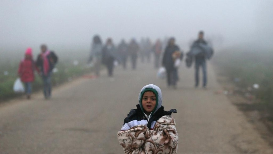 A migrant boy walks with other migrants on the road near a border between Serbia and Croatia, near the village of Berkasovo, Serbia, Thursday, Oct. 22, 2015. Many migrants from the Middle East, Asia and Africa expressed bewilderment and disappointment because they had been told as they began their journeys in Turkey that the hard part would end once they reached EU countries like Croatia and Slovenia. (AP Photo/Darko Vojinovic)