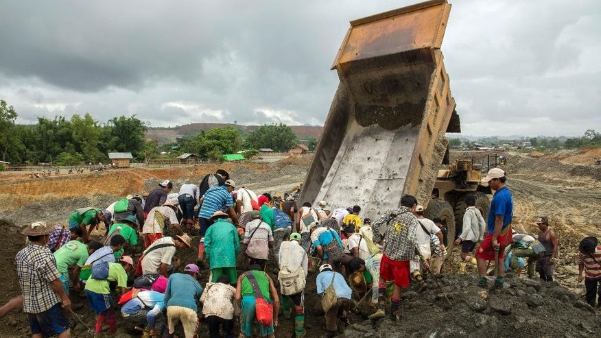 In this June 16, 2015 photo, freelance jade miners search for raw jade stones in an earth dump from a company's truck in Hpakant area, Kachin State, Northern Myanmar. Uncontrolled mining of Myanmar's famously valuable jade deposits is enriching individuals and companies tied to the country's former military rulers while exacting a growing human and environmental toll on impoverished Kachin state. (AP Photo/Hkun Lat)