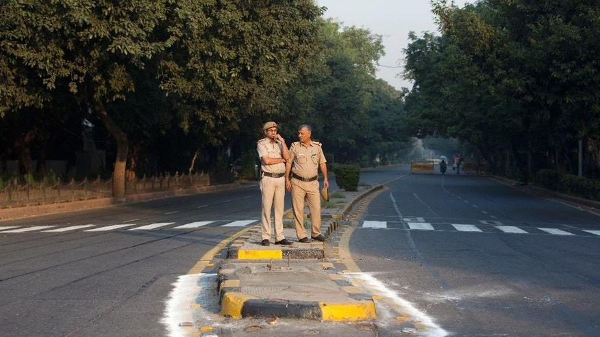 Indian policemen stand and wait for cyclists during a car-free day covered only a six-kilometer (4-mile) stretch in New Delhi, India, Thursday, Oct. 22, 2015. The world's most polluted capital, New Delhi, closed a major stretch of road to private cars for a few hours, hoping to give its citizens a brief breath of fresh air by observing a car-free day. (AP Photo/Tsering Topgyal)