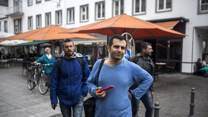 In this Sept. 16, 2015, photo, Osman al-Haj Osman, center, walks across a street in Saarlouis, Germany, with his friends Mohammed al-Haj, left, and Dr. Ahmed Naasan, who recently arrived from Aleppo, Syria. Osman, a 33-year-old surgeon, is haunted by doubt whether he made the right decision in immigrating to such a different world, as well as burdened by memories of the horrors of the civil war that he escaped when he fled his home city of Aleppo in northern Syria more than a year ago. (AP Photo/Santi Palacios)