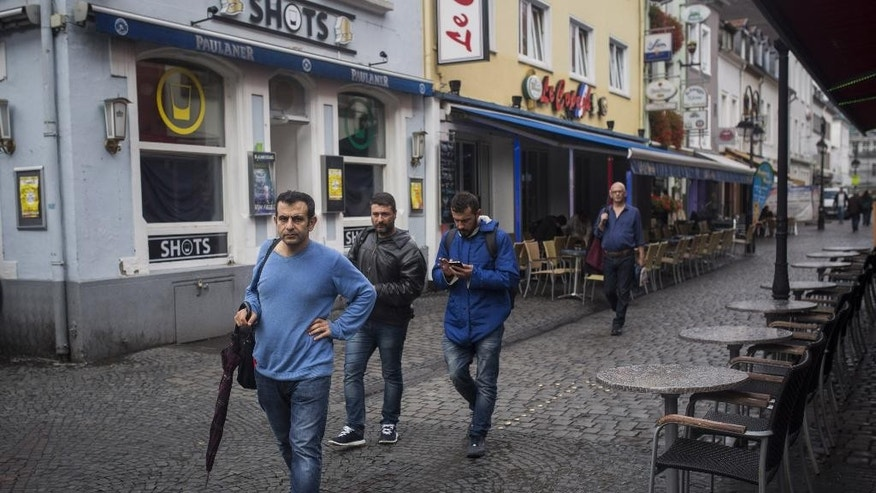 In this Sept. 16, 2015, photo. Osman al-Haj Osman, front left, walks across a street in Saarlouis, Germany, with his friends Mohammed al-Haj, third from left, and Dr, Ahmed Naasan, second from left, who recently arrived from Aleppo, Syria. Osman, a 33-year-old surgeon, is haunted by doubt whether he made the right decision in immigrating to such a different world, as well as burdened by memories of the horrors of the civil war that he escaped when he fled his home city of Aleppo in northern Syria more than a year ago. (AP Photo/Santi Palacios)