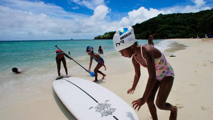 FILE - In this June 13, 2009 file photo, children play at a resort beach in Ngerkebesang, Palau. Lawmakers in the tiny Pacific island nation of Palau passed a law Thursday, Oct. 22, 2015 to make almost all its coastal waters a marine sanctuary in the latest move to expand ocean protections. A news release said Palau's president plans to sign the legislation next week. Friday is a national holiday in Palau. (AP Photo/Itsuo Inouye, File)