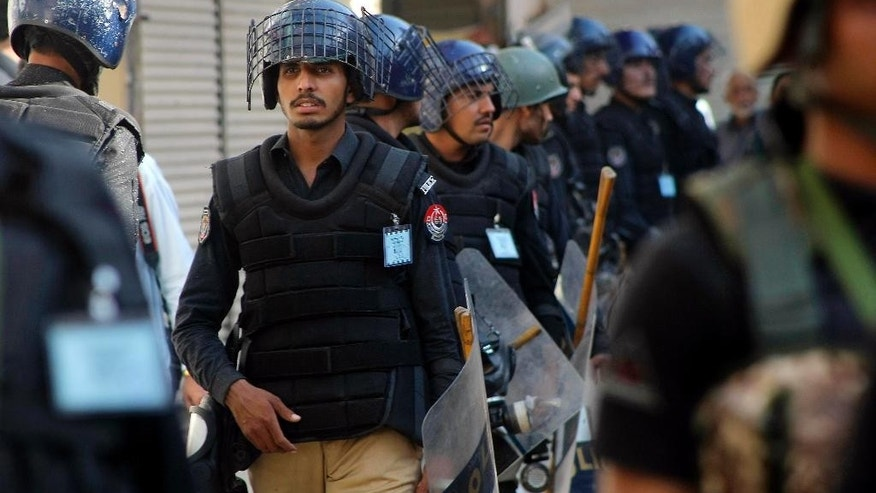 Pakistani police officers guard a Shiite procession during Muharram in Peshawar, Pakistan, Thursday, Oct. 22, 2015. A government official says a powerful bomb at a Shiite mosque in southwest Pakistan has killed many people and wounded several others. (AP Photo/Mohammad Sajjad)
