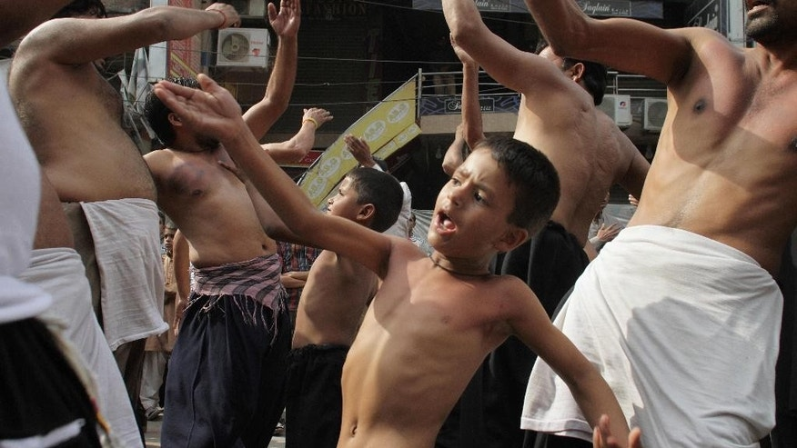 Pakistani Shiite mourners beat their chests during the month of Muharram ahead of Ashoura day, in Lahore, Pakistan, Thursday, Oct. 22, 2015. Ashoura is a Shiite Muslim commemoration marking the death of Hussein, the Prophet Muhammad's grandson, at the Battle of Karbala in present-day Iraq. (AP Photo/K.M. Chaudary)