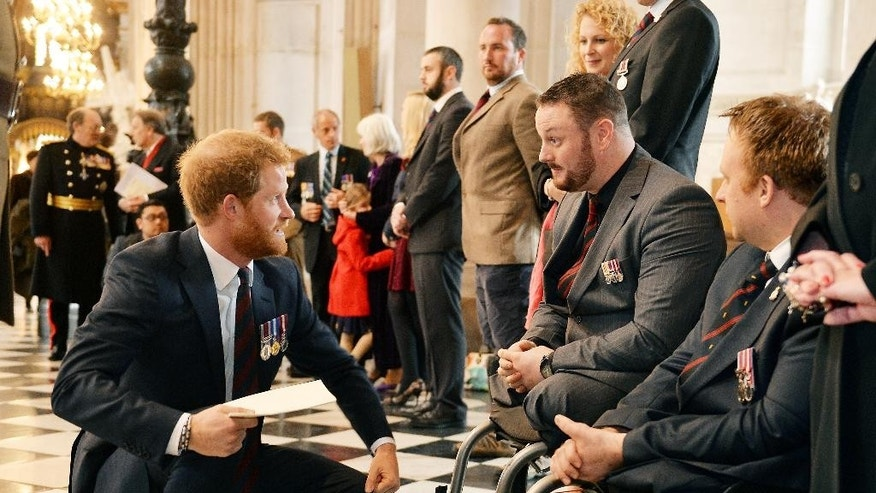 Britain's Prince Harry, left, talks to Sapper Clive Smith, 2nd right, and Sapper Jack Cummings, right, who both lost their legs in Afghanistan in 2010 at St Paul's Cathedral, London, following a service marking the 75th anniversary of Explosive Ordnance Disposal (EOD) across the Armed Forces., Thursday, Oct. 22, 2015. (John Stillwell/Pool Photo via AP)