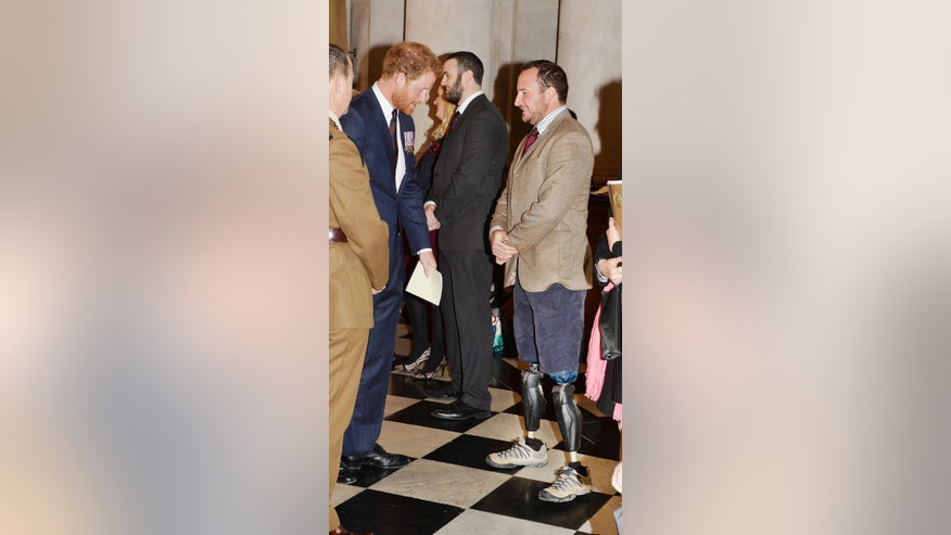 Britain's Prince Harry talks to Luke Sinnott who lost both his legs in Afghanistan in 2010 at St Paul's Cathedral, London, following a service marking the 75th anniversary of Explosive Ordnance Disposal (EOD) across the Armed Forces, Thursday, Oct. 22, 2015. (John Stillwell/Pool Photo via AP)