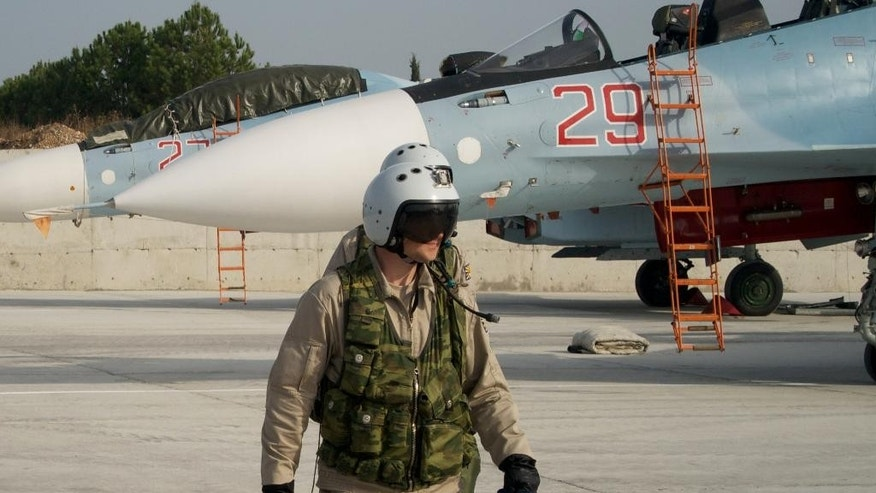 A Russian pilot walks from his Su-30 jet in the background at Hemeimeem airbase, Syria, on Thursday, Oct. 22, 2015. Since early morning, Russian combat jets have been taking off from this base in western Syria, heading for missions. (AP Photo/Vladimir Isachenkov)