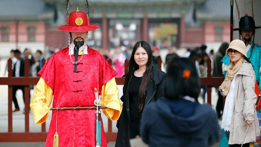 Visitors take their souvenir photo at the Gyeongbok Palace, one of South Korea's well-known landmarks, in Seoul, South Korea, Friday, Oct. 23, 2015. South Korea's economy expanded 2.6 percent in the July-September quarter from a year ago, the fastest clip in three quarters, the Bank of Korea said Friday, showing a recovery from the Middle Eastern respiratory syndrome crisis that gripped the country in the summer.  (AP Photo/Lee Jin-man)
