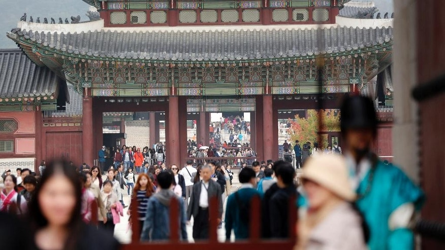 Tourists visit the Gyeongbok Palace, one of South Korea's well-known landmarks, in Seoul, South Korea, Friday, Oct. 23, 2015. South Korea's economy expanded 2.6 percent in the July-September quarter from a year ago, the fastest clip in three quarters, the Bank of Korea said Friday, showing a recovery from the Middle Eastern respiratory syndrome crisis that gripped the country in the summer. (AP Photo/Lee Jin-man)