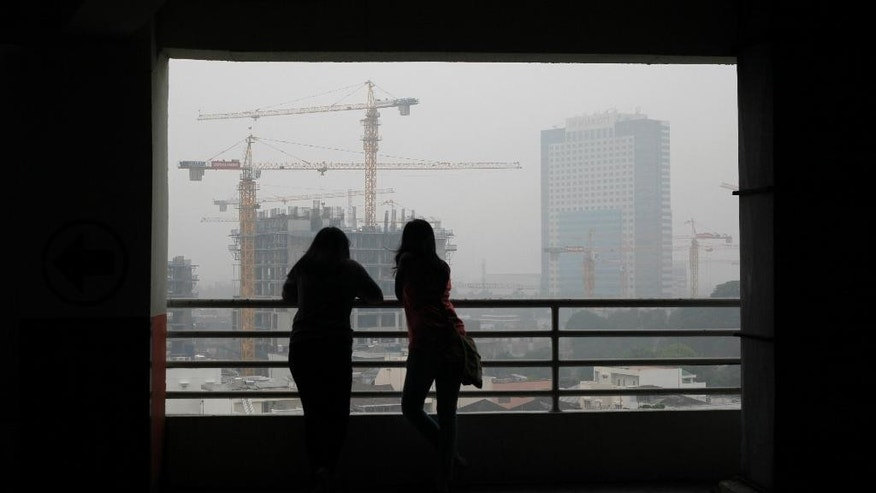 Indonesian women are silhouetted against the city skyline which is shrouded by the haze from forest fires, in Medan, North Sumatra, Indonesia, Thursday, Oct. 22, 2015. Southern Thailand was hit Thursday by the most severe haze ever from forest fires in Indonesia, forcing all schools in a province to close and disrupting flights in a popular tourist area, officials said. (AP Photo/Binsar Bakkara)