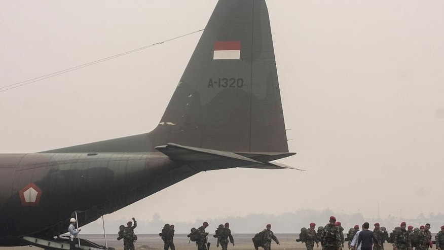 Indonesian soldiers who are deployed to help containing massive forest and land fires that have caused widespread haze in parts of Southeast Asia, disembark from an military cargo plane upon arrival at the airbase in Palembang, South Sumatra, Indonesia, Thursday, Oct. 22, 2015. Southern Thailand was hit Thursday by the most severe haze ever from forest fires in Indonesia, forcing all schools in a province to close and disrupting flights in a popular tourist area, officials said. (AP Photo/Bagus Kurniawan)