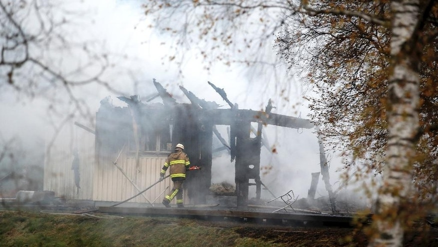 FILE - A Tuesday, Oct. 20, 2015 photo from files showing a firefighter working in the smoking remains of an accommodation home for asylum seekers near Munkedal in western Sweden. 14 people were safely evacuated from the conflagration that Swedish police are investigating as suspected arson. No one was hurt. But it was among a spate of fires at asylum facilities raising concerns that the Scandinavian country's generous policy toward migrants is under a serious backlash. (AP Photo/Adam Ihse, file)   SWEDEN OUT