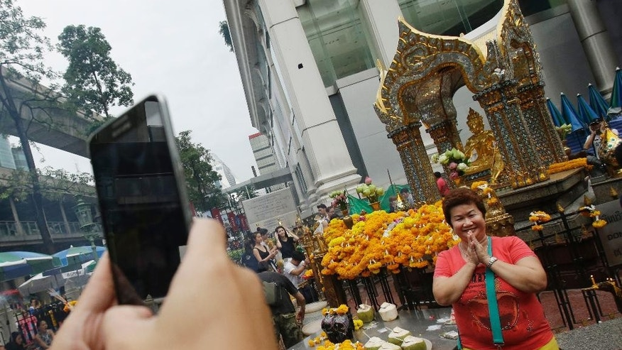 Asian tourists takes a picture in front of the Erawan Shrine in Bangkok, Thailand, Thursday, Oct. 22, 2015. A deadly bombing in August threatened to scuttle Thailand's economically crucial tourism industry but officials are now forecasting more than 30 million visitors this year as arrivals from China swell. (AP Photo/Sakchai Lalit)