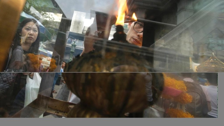 A Chinese tourist lights an incense stick to make an offering for Phra Phrom, the Thai interpretation of the Hindu god Brahma, at the Erawan Shrine in Bangkok, Thailand, Thursday, Oct. 22, 2015. A deadly bombing in August threatened to scuttle Thailand's economically crucial tourism industry but officials are now forecasting more than 30 million visitors this year as arrivals from China swell. (AP Photo/Sakchai Lalit)
