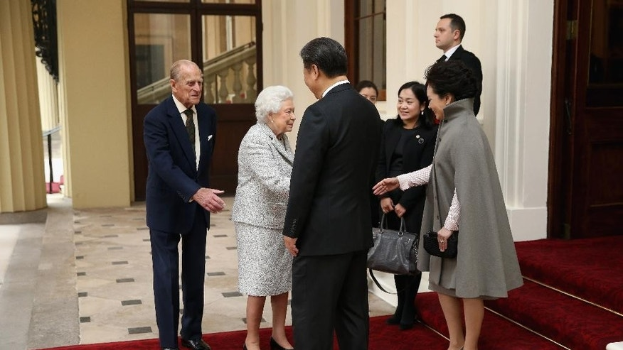 Britain's Queen Elizabeth II, 2nd left, and Prince Philip, Duke of Edinburgh, left, bid farewell to President of the People's Republic of China, Xi Jinping, back to camera, and his wife, Madame Peng Liyuan from Buckingham Palace on Thursday Oct. 22, 2015, in London. The President of China,  Xi Jinping and his wife, are ending a State Visit to the United Kingdom as guests, staying at Buckingham Palace as guests of The Queen. (Chris Jackson / pool via AP)