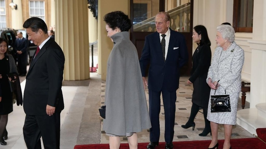 Britain's Queen Elizabeth II, right, and Prince Philip, Duke of Edinburgh bid farewell to President of the People's Republic of China, Xi Jinping, left, and his wife, Madame Peng Liyuan from Buckingham Palace on Thursday Oct. 22, 2015, in London. The President of China,  Xi Jinping and his wife, are ending a State Visit to the United Kingdom as guests, staying at Buckingham Palace as guests of The Queen. (Chris Jackson / pool via AP)